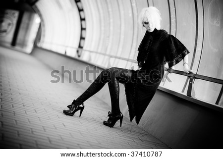 Goth woman in industrial tunnel. Contrast dark colors. - stock photo