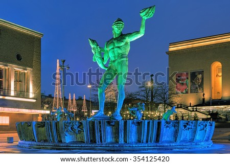 GOTHENBURG, SWEDEN - DECEMBER 15, 2015: Poseidon Fountain with green-blue illumination in the evening. The fountain was designed by swedish sculptor Carl Milles and was unveiled on November 20, 1927. - stock photo