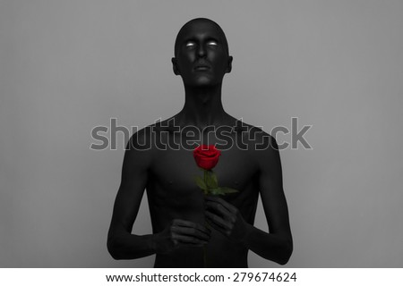 Gothic and Halloween theme: a man with black skin holding a red rose, black death isolated on a gray background in studio - stock photo