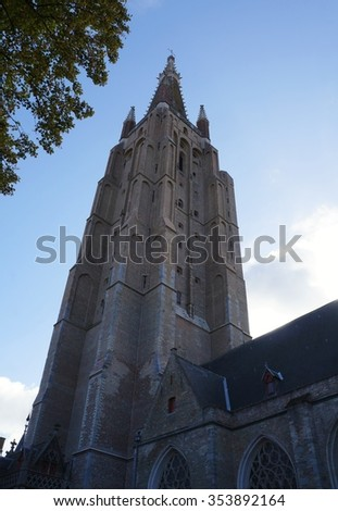 Gothic architecture, beautiful buildings and church tower in historical town of Bruges, Belgium - stock photo