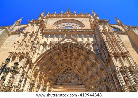 Gothic decorations above a gate to the Cathedral of Saint Mary of the See (Seville Cathedral) in sunny day, Seville, Andalusia, Spain - stock photo