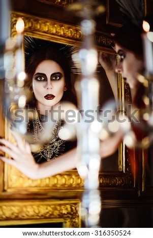 Gothic fashion: mysterious beautiful young woman looking into the mirror - stock photo