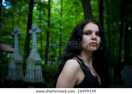 Gothic girl walking through cemetery crosses on background - stock photo