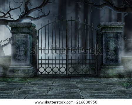 Gothic graveyard gate with old withered trees - stock photo