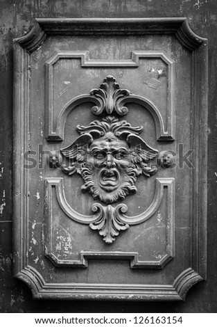 Gothic mask on an old wodden door in Milan - Italy - stock photo
