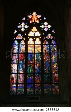 Gothic stained glass window in St. Vitus cathedral in Prague portraying the Pentecost - stock photo