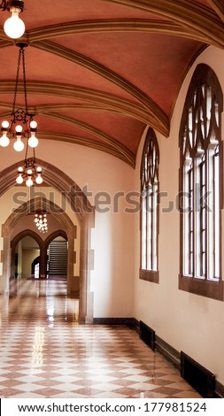 Gothic style hallway with windows letting in the afternoon sunlight - stock photo