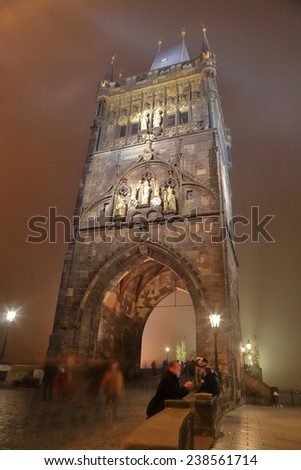 Gothic tower at the end of the Charles bridge in foggy night, Prague, Czech Republic - stock photo