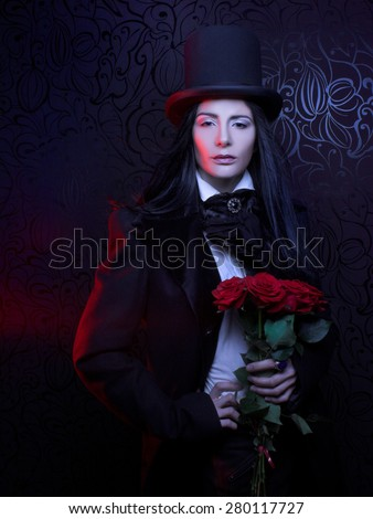 Gothic Valentine. Romantic portrait of young woman in gothic man image posing with red roses.