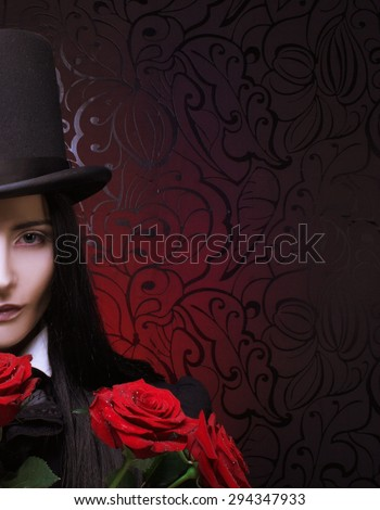 Gothic Valentine. Romantic portrait of young woman in gothic man image posing with red roses