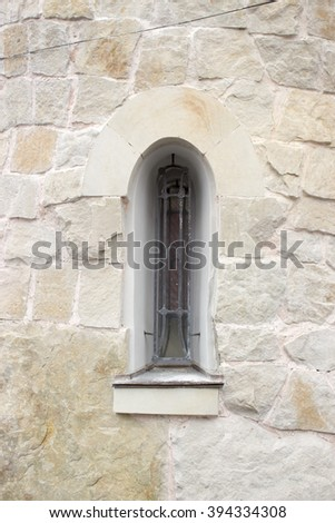 Gothic window in stone wall - stock photo