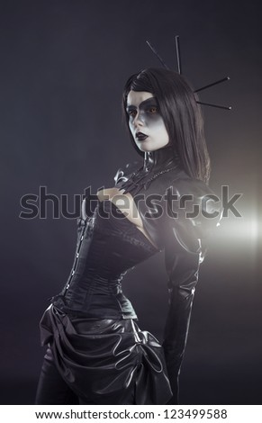 Gothic woman in black Victorian outfit wearing tight corset and bolero - stock photo