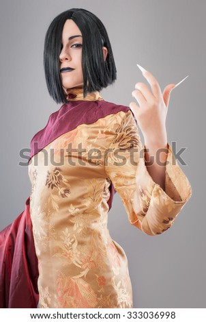 Gothic woman with chinese nails. Dark gothic woman with cloak and chinese nails - stock photo
