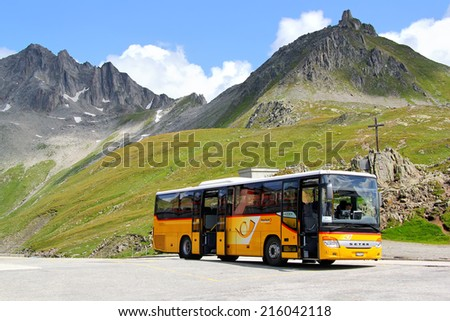 GOTTHARD PASS, SWITZERLAND - AUGUST 5, 2014: Yellow Setra S415H interurban coach at the high Alpine mountain road. - stock photo