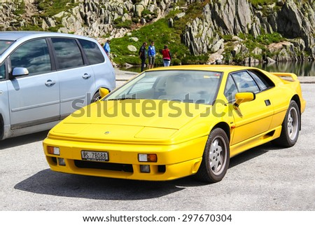GOTTHARD PASS, SWITZERLAND - AUGUST 5, 2014: Yellow supercar Lotus Esprit at the high mountain Alpine road. - stock photo