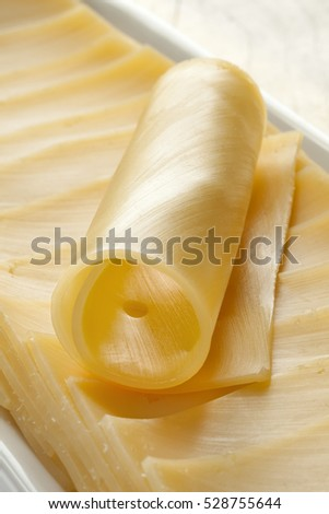 Gouda cheese in slices and a roll
