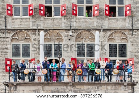 GOUDA-HOLLAND-AUG. 21, 2014. People watching traditional cheese market at balcony of the ancient city hall. Gouda is world famous for its cheese, which is still traded on cheese market, each Thursday. - stock photo