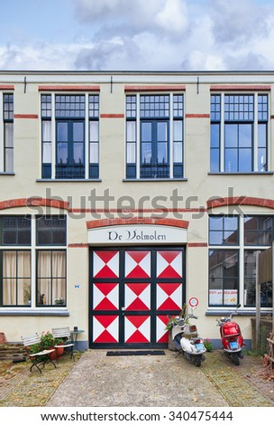 GOUDA-HOLLAND-OCTOBER 13, 2015. De Volmolen at Gouda. A mansion as part of an ancient windmill.  Volmolen is an industry mill that was used for finishing of woven wool fabric to improve its quality. - stock photo