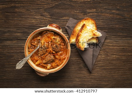 Goulash cabbage with beef on wooden background.