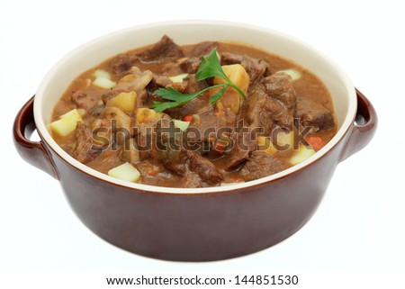 Goulash in a pot on white background - stock photo