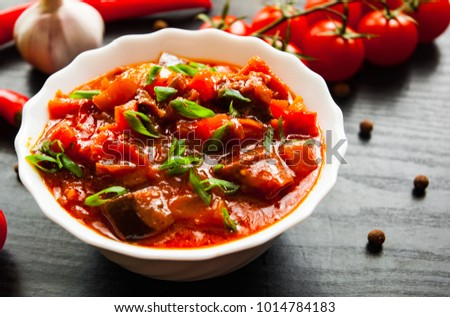 Goulash. Vegetable rague with eggplant, pepper, tomato and carrot in white bowl on dark wooden background