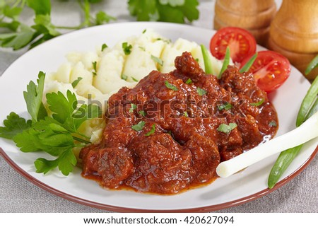 Goulash with mashed potatoes and tomato