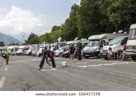 GOURETTE,FRANCE-JUL 15:A man painting on the road to mountain pass Aubisque,in Pyrenees Mountains, before the appearance of the cyclists in the 13th stage of Le Tour de France on July 15 2011.