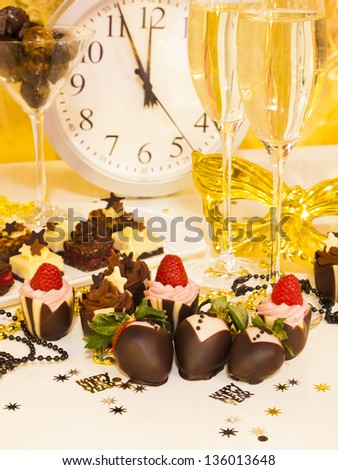 Gourmet assorted petite party pastries decorated for New Year Eve celebration. - stock photo