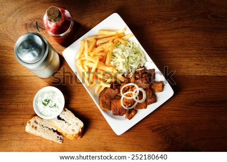 Gourmet Beef Steak, French Fries and Shredded Cabbage on Wooden Table with Bread and Sauce. - stock photo