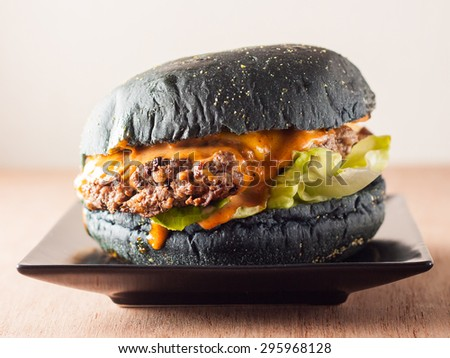 Gourmet black burger with Spicy sauce on wooden table and black background - stock photo