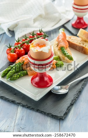 Gourmet breakfast with soft boiled egg, green asparagus and smoked salmon - stock photo