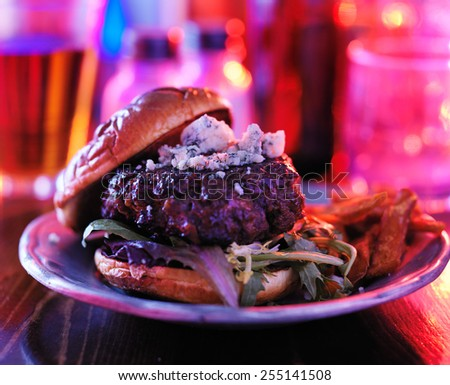 gourmet burger at pub or bar with colorful lighting - stock photo