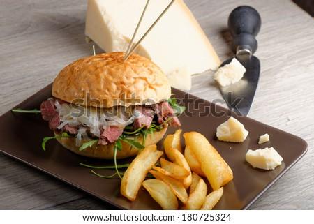Gourmet burger with roast beef, potato and parmesan cheese, close up - stock photo