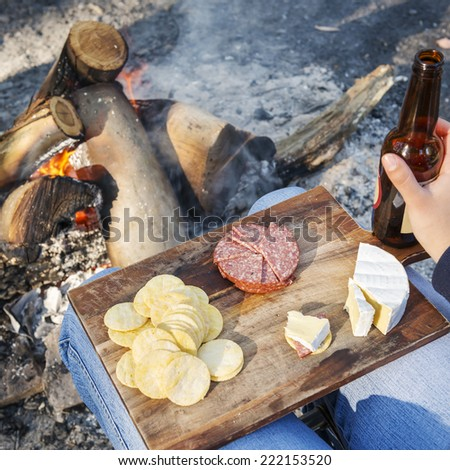 Gourmet camping food on a wooden board, with cheese, salami and crackers with a beer in front of the fire - stock photo