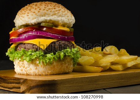 Gourmet Cheeseburger & Chips - Burger and thick cut chips on a black background. Low key lighting. - stock photo