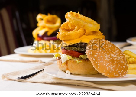 Gourmet Cheeseburgers Piled High with Toppings on Plates on Restuarant Table - stock photo