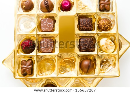 Gourmet chocolates in golden box on a white background.