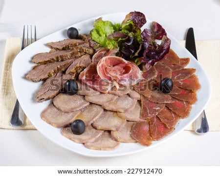 Gourmet cold meat platter on a buffet with assorted smoked and processed meats garnished with fresh lettuce and olives, high angle view - stock photo