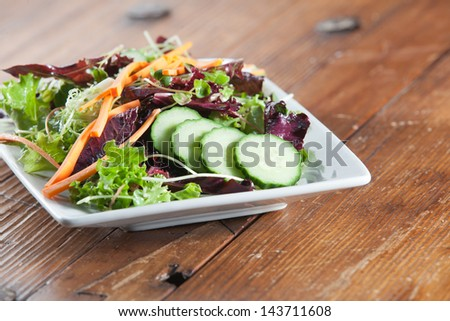 Gourmet colorful and healthy arugula and fennel salad in a rustic setting on an antique wooden table. - stock photo