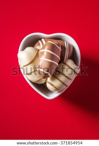 Gourmet date chocolates in a small heart shape bowl on bright red background, View from above.  - stock photo