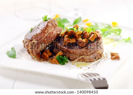 Gourmet dinner of thick juicy medallions of fillet steak tied with string topped with wild mushrooms and served garnished with herbs on a white platter - stock photo