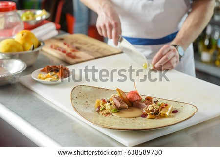 Gourmet dish on vintage plate, close-up. Chef cutting vegetables on the background. Restaurant kitchen.