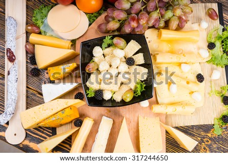 Gourmet display of different cheeses arranged around a wooden board on a buffet table with a central bowl filled with diced cheese, cocktail onions and olives, overhead view - stock photo