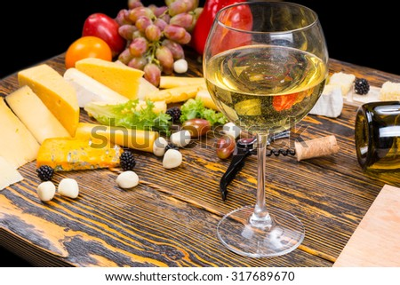 Gourmet Food Still Life - Close Up of Glass of White Wine Amongst Variety of Cheeses and Fresh Fruit on Rustic Wooden Table with Copy Space - stock photo
