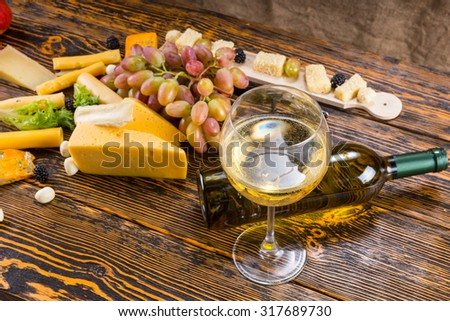 Gourmet Food Still Life - Close Up of Glass of White Wine with Fallen Bottle Amongst Variety of Cheeses and Fresh Fruit on Rustic Wooden Table with Copy Space - stock photo