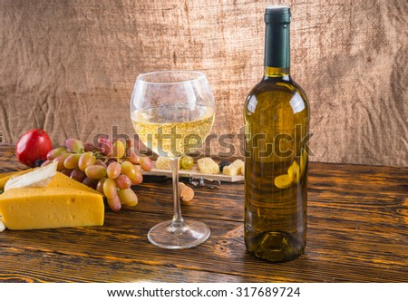 Gourmet Food Still Life - Close Up of White Wine in Glass Next to Bottle on Rustic Wooden Table with Cheese and Grapes - stock photo