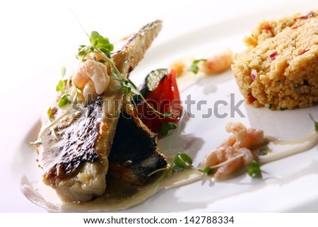 Gourmet grilled fish served with prawns and garnish