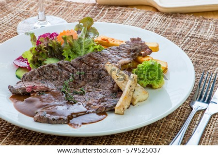 Gourmet grilled steak flavoured with basil beef steak with Roasted pumpkin and fresh green herb salad
