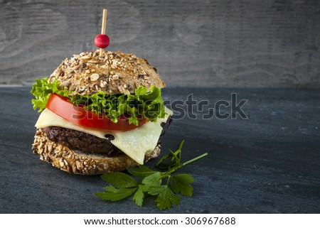 Gourmet hamburger with swiss cheese, fresh vegetables on multigrain bun against dark background and copy space - stock photo