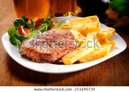 Gourmet Healthy Grilled Beef and Potato French Fries on White Plate with Herbs and Veggies. Placed on Wooden Table. - stock photo